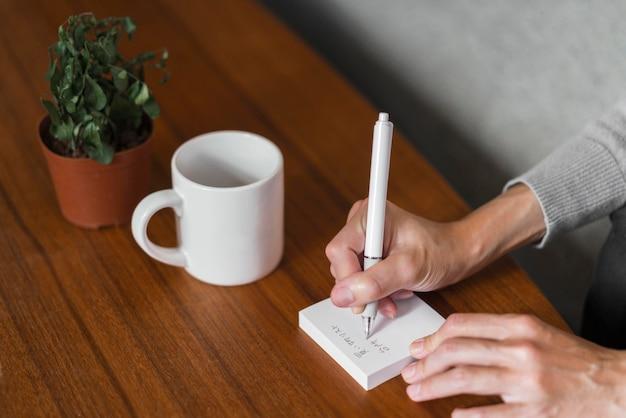 Zbliżenie dłoni pisania na karteczkę