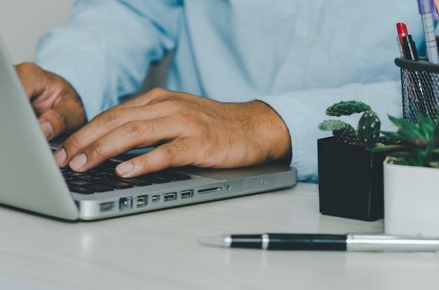Zbliżenie dłoni pisania na klawiaturze laptopa komputera