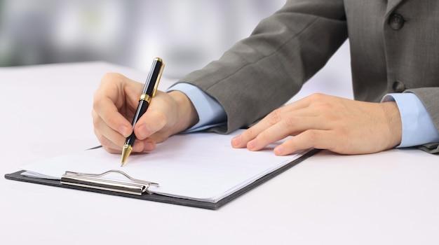 Zbliżenie dłoni pisania w mleczarni biznesowych.