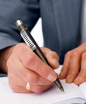 Zbliżenie dłoni pisania w mleczarni biznesowych