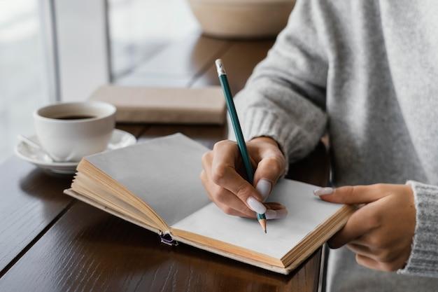 Zbliżenie dłoni pisania w notesie