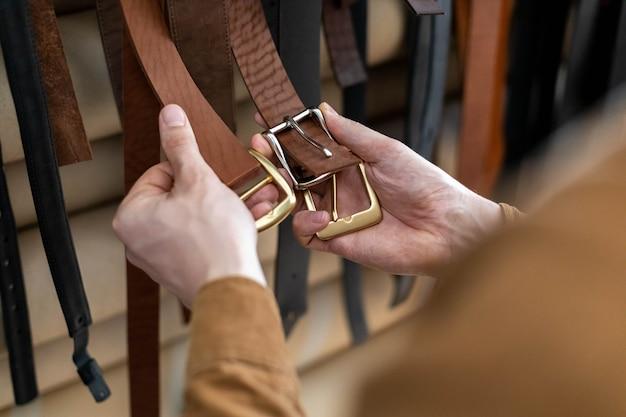 Zbliżenie dłoni profesjonalnego garbarza wybierającego klamrę do paska na drewnianym stole w warsztacie skórzanym