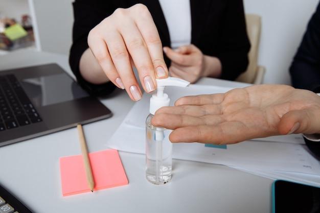 Zbliżenie dłoni przy użyciu żelu antyseptycznego do dezynfekcji rąk nad biurkiem w biurze