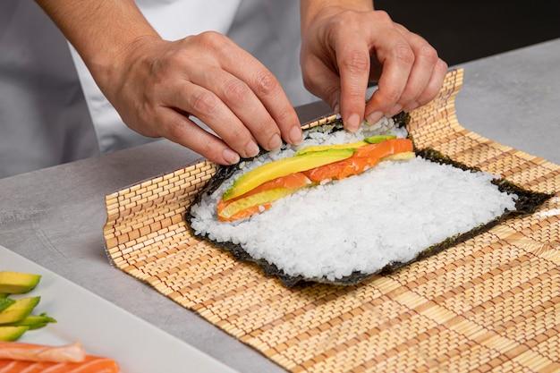 Zbliżenie dłoni przygotowując smaczne sushi