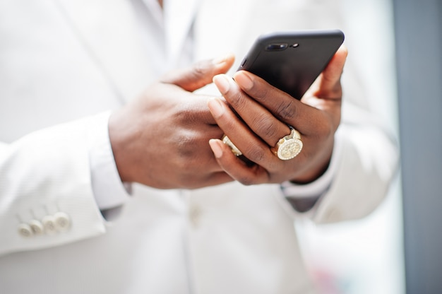 Zbliżenie dłoni przystojny mężczyzna afroamerykanów w formalnej odzieży, patrząc na telefon komórkowy.