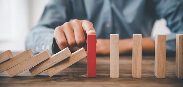 Zbliżenie dłoni ręka biznesmena, który zatrzymuje lub zapobiega spadającym blokom. koncepcja ochrony przed ryzykiem, eliminując ryzyko