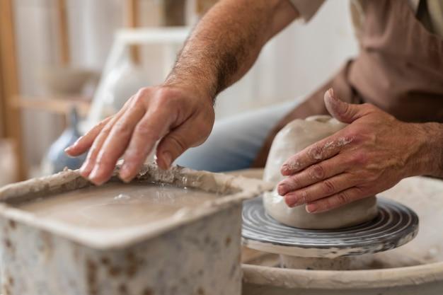 Zbliżenie dłoni robiących ceramikę