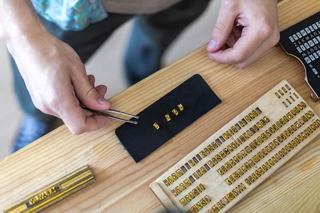 Zbliżenie dłoni rzemieślnika, wpisując tekst do znakowania skóry z osobistym stemplem, tworząc etykietę rzemieślniczą