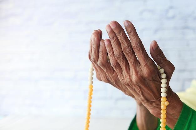Zbliżenie dłoni starszych kobiet modląc się w ramadan