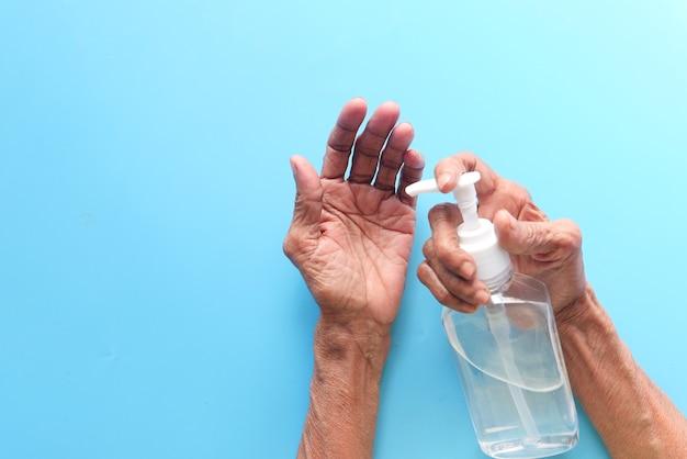 Zbliżenie dłoni starszych kobiet za pomocą żelu dezynfekującego do zapobiegania wirusom.