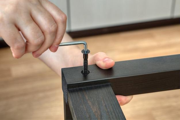 Zbliżenie dłoni stolarza kluczem sześciokątnym, przykręcić śrubę do mebli w drewnianą deskę.