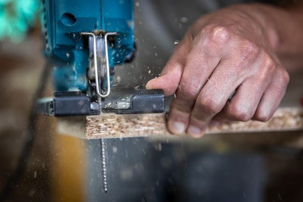 Zbliżenie dłoni stolarza w procesie cięcia drewna za pomocą wyrzynarki.