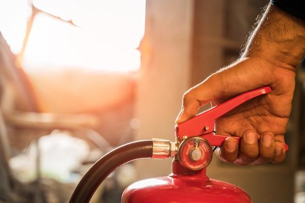 Zbliżenie dłoni strażak za pomocą walki gaśnicy.