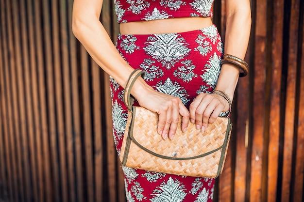 Zbliżenie dłoni stylowej kobiety trzymającej torebkę ze słomy