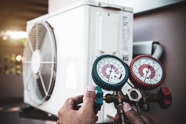 Zbliżenie dłoni technika za pomocą manometru do napełniania klimatyzatorów.
