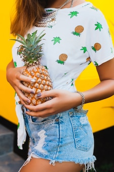 Zbliżenie dłoni trzymając ananas opaloną skórę atrakcyjnej kobiety na wakacjach w słomkowym kapeluszu boso w dżinsowych szortach z nadrukiem t-shirt letnia moda