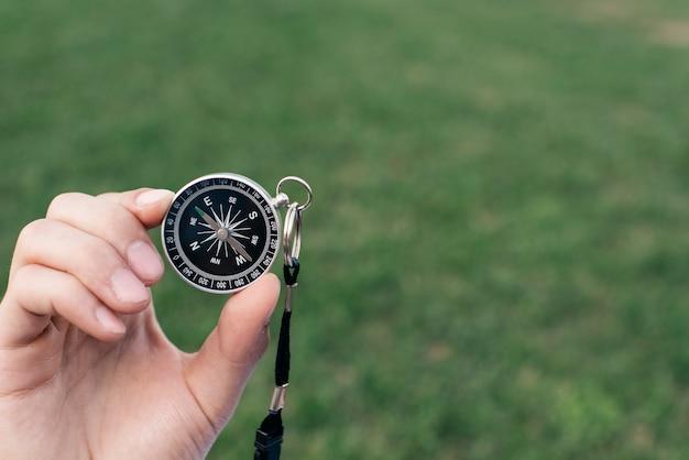 Zbliżenie dłoni trzymając kompas nawigacyjny przeciwko zielone tło zamazane pole
