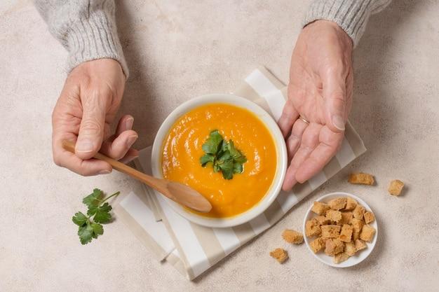 Zbliżenie dłoni trzymając łyżkę i miskę