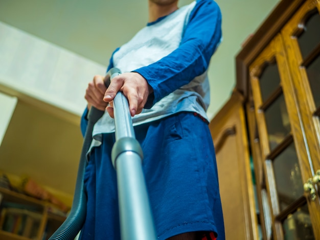 Zbliżenie dłoni trzymając odkurzacz na dywanie w pokoju