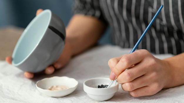 Zbliżenie dłoni trzymając pędzel do malowania