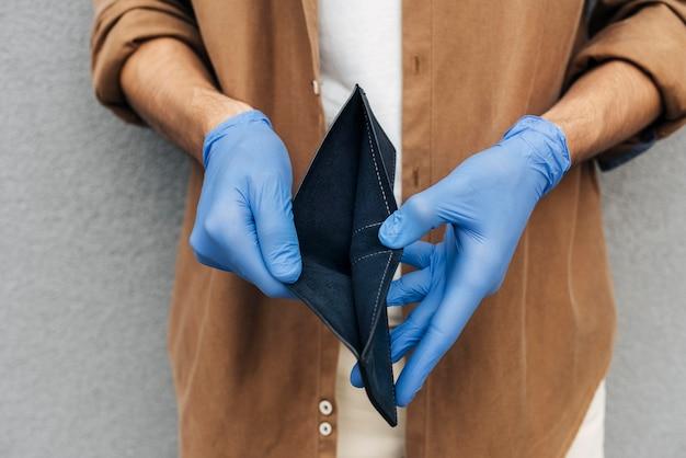 Zbliżenie dłoni trzymając portfel w rękawiczkach