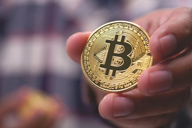 Zbliżenie dłoni trzymającej bitcoin
