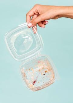 Zbliżenie dłoni trzymającej brudne plastikowe pudełko