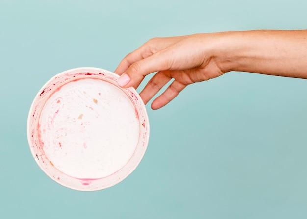 Zbliżenie dłoni trzymającej brudny talerz