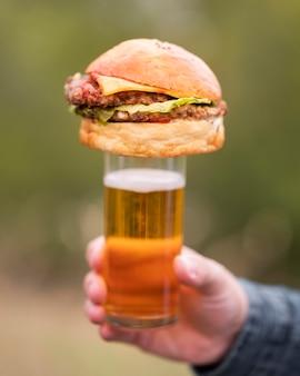 Zbliżenie dłoni trzymającej burgera na szczycie szkła