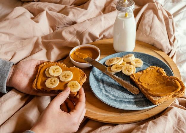 Zbliżenie dłoni trzymającej chleb z masłem orzechowym