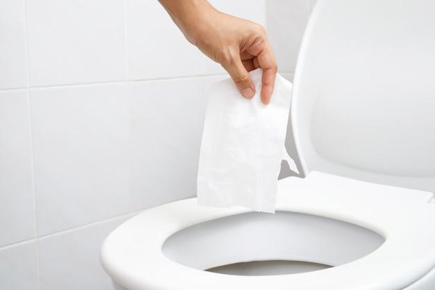 Zbliżenie dłoni trzymającej chusteczkę do wrzucenia do muszli klozetowej. nie można spuścić wody z papieru toaletowego, co może spowodować zatkanie stolca. toaleta