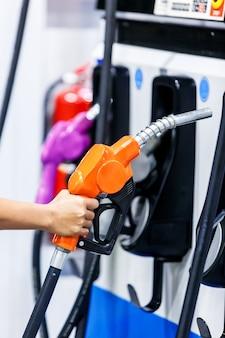 Zbliżenie dłoni trzymającej dyszę paliwową na stacji benzynowej