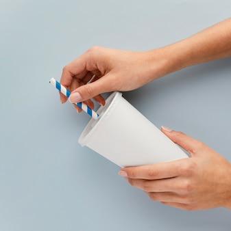 Zbliżenie dłoni trzymającej filiżankę i słomkę