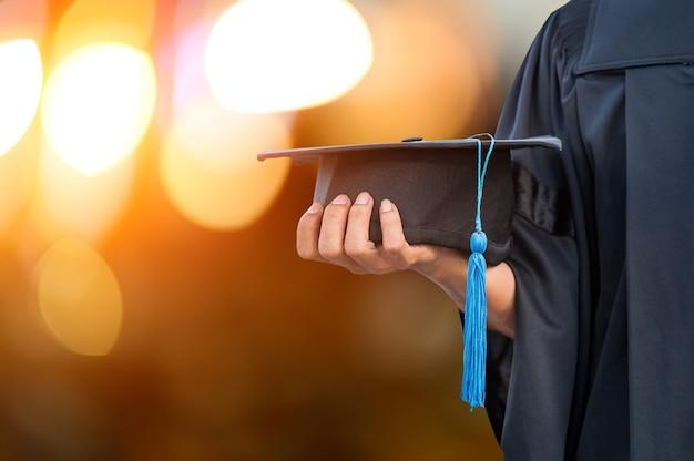 Zbliżenie dłoni trzymającej kapelusz ukończenia szkoły