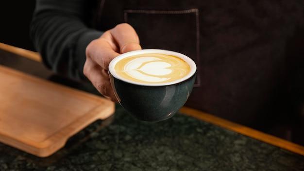Zbliżenie dłoni trzymającej kawę z mlekiem