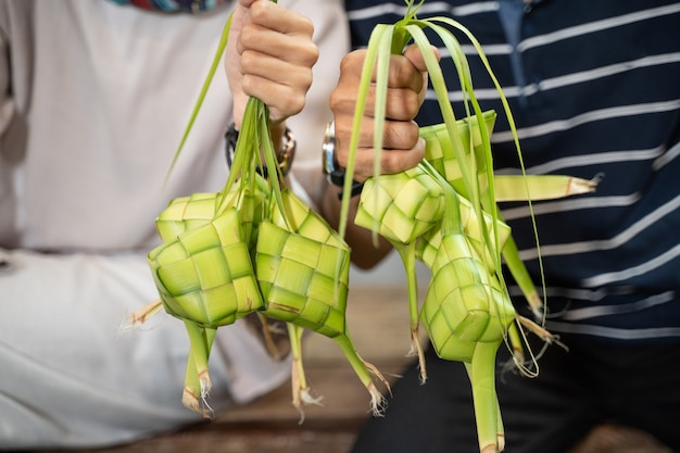 Zbliżenie dłoni trzymającej ketupat z liściem kokosowym