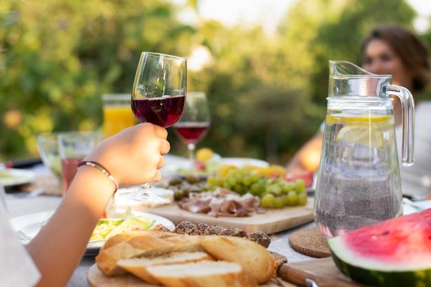 Zbliżenie dłoni trzymającej kieliszek do wina