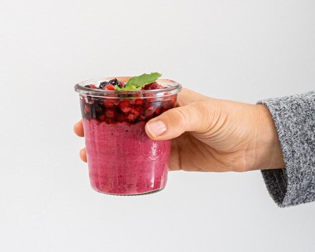 Zbliżenie dłoni trzymającej kieliszek smoothie