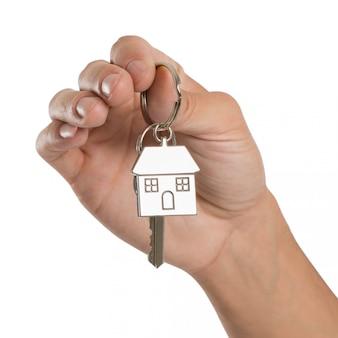 Zbliżenie dłoni trzymającej klucz domu samodzielnie na białym tle
