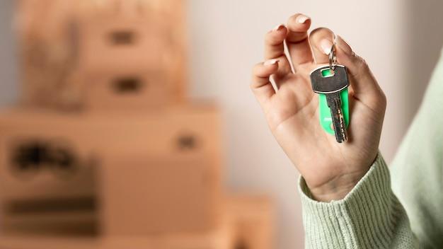 Zbliżenie dłoni trzymającej klucze w pomieszczeniu