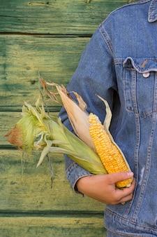 Zbliżenie dłoni trzymającej kukurydzę