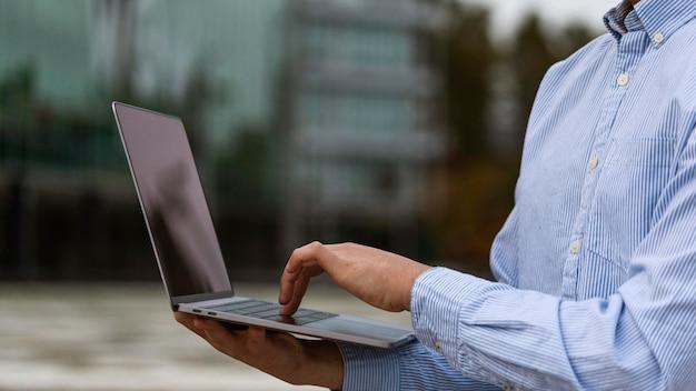 Zbliżenie dłoni trzymającej laptopa na zewnątrz