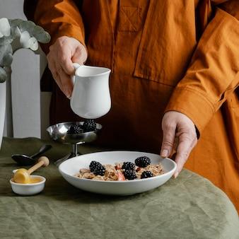 Zbliżenie dłoni trzymającej miskę z płatków zbożowych