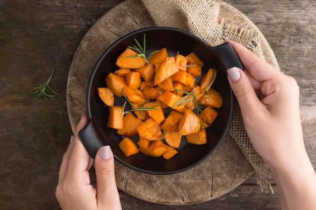 Zbliżenie dłoni trzymającej miskę z ziemniakami