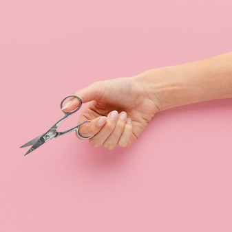 Zbliżenie dłoni trzymającej nożyczki do paznokci