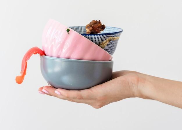 Zbliżenie dłoni trzymającej odpady z plastikowymi miskami