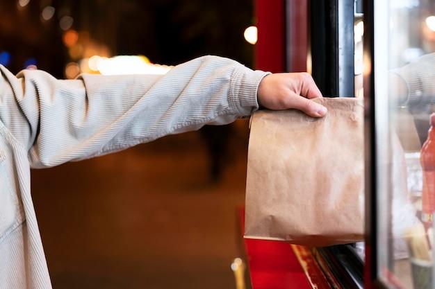 Zbliżenie dłoni trzymającej papierową torbę