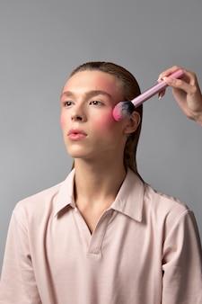 Zbliżenie dłoni trzymającej pędzel do makijażu