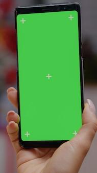 Zbliżenie dłoni trzymającej pionowo smartfona z zielonym ekranem