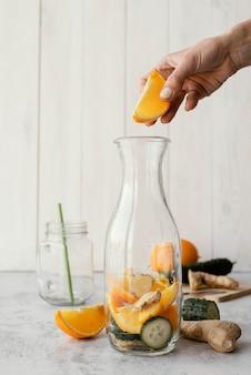 Zbliżenie dłoni trzymającej plasterek pomarańczy